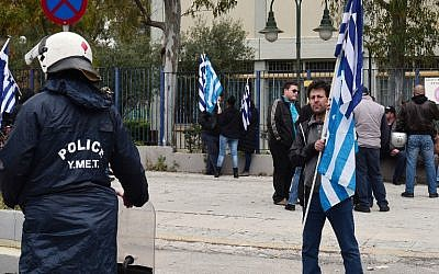 Police cordon off Golden Dawn party supporters carrying Greek flags, outside the high security prison in Korydallos near Athens on April 20, 2015. (photo credit: AFP)