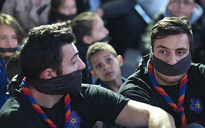 Men wearing gags and scarves in the colours of the Armenian flag on April 23, 2015, in Marseille, southeastern France, during a commemoration on the eve of the 100th anniversary of the genocide of 1.5 million Armenians by Ottoman forces.(photo credit: AFP/BORIS HORVAT)