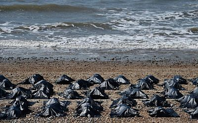 'Body bags' appear on Brighton beach in southern England, on April 22, 2015, in a display by Amnesty International to highlight what they claim is Britain's shameful response to the refugee and migrant crisis in the Mediterranean. (Ben Stansall/AFP)
