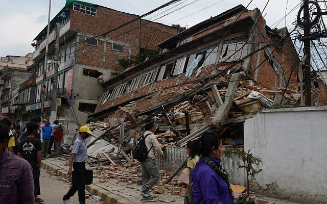 Nepalese people walk past a collapsed bullding in Kathmandu after an earthquake on April 25, 2015. (photo credit: AFP/PRAKASH MATHEMA)