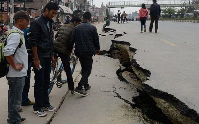 Nepalese residents walk past road damage after an earthquake in Kathmandu, Nepal, on April 26, 2015. (photo credit: AFP/Prakash Mathema)