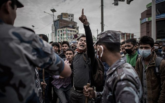 Nepalese riot police officials stand alert on a street in Kathmandu on April 29, 2015, as earthquake survivors desperate to leave the Nepalese capital show their anger after promised special bus services failed to materialize. (photo credit: AFP/Philippe LOPEZ)