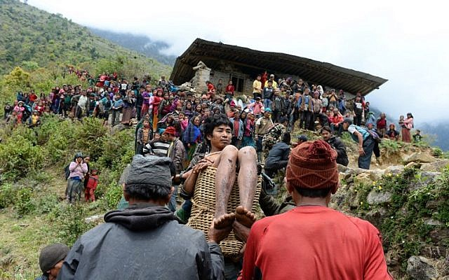 Villagers carry an injured youth in a basket down the hill-side to an Indian Army helicopter at Uiya village, in northern-central Gorkha district on April 29, 2015.  (photo credit: AFP PHOTO / SAJJAD HUSSAIN)