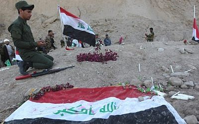 An Iraqi Shiite fighter prays at a burial site believed to hold victims of a June 2014 massacre in which hundreds of army cadets were executed by the Islamic State group, in the city of Tikrit, on April 4, 2015. (AFP/AHMAD AL-RUBAYE)