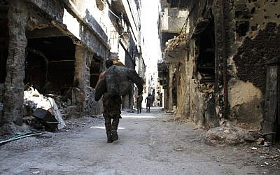 Men walk past destroyed buildings in the Yarmouk Palestinian refugee camp in the Syrian capital Damascus on April 6, 2015. (AFP/Youssef Karwashan)
