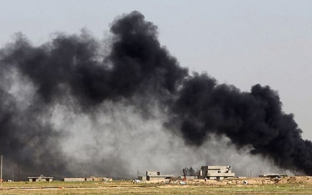 Smoke billows from what is believed to be an oil field which was set alight by Islamic State (IS) group militants in the Mkeishifa area, south of the northern Iraqi city of Tikrit, as government forces, supported by Popular Mobilization units, try to retake the area from Islamist rebels on April 9, 2015. (photo credit: AFP PHOTO / AHMAD AL-RUBAYE)