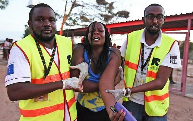 Paramedics help a student who was injured during an attack by Somalia's al-Qaeda-linked al-Shabab gunmen on the Garissa University campus in Garissa on April 2, 2015. (photo credit: AFP/ Carl Dd Souza)