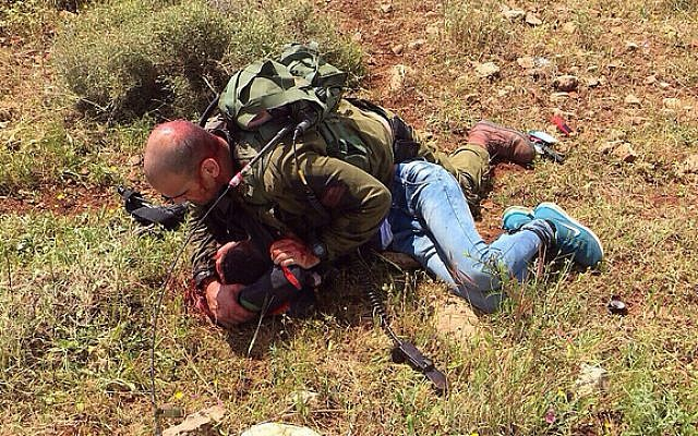 An Israeli soldier pins down a Palestinian man who stabbed another soldier near the West Bank security fence, April 2, 2015 (photo credit: IDF spokesperson)