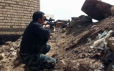 A member of the Iraqi security forces aims his weapon to attack Islamic State group militants on al-Houz bridge on the Euphrates river in Ramadi, 70 miles (115 kilometers) west of Baghdad, Iraq, Friday, April 24, 2015. (Photo credit: AP)