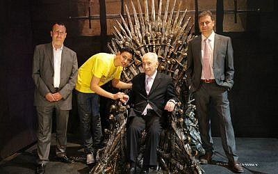 Shimon Peres sits in the Iron Throne of the famed series 'Game of Thrones,' with British Ambassador Matthew Gould on his right, YES CEO Ron Eilon (left) and 17-year old Ben Yuval, an avid fan of the series, who is suffering from a hematological disease and was hosted by Lehoshit Yad Association (Courtesy YES)