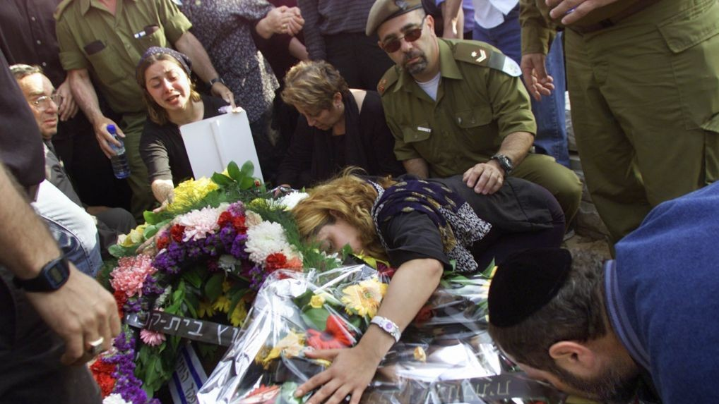 Family members of Avner Yaskov cry over his grave during a funeral ceremony in the southern Israeli town of Beersheba, April 10, 2002. Yaskov was killed, along with 12 other Israeli soldiers, during operations in the West Bank town of Jenin. (photo credit:A P Photo/David Guttenfelder)