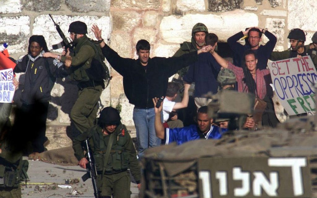 Under the cover of an Israeli army tank (foreground), Israeli soldiers arrest international peace activists holding placards outside the Church of Nativity in the West Bank town of Bethlehem, April 28, 2002. (photo credit: AP/Lefteris Pitarakis)