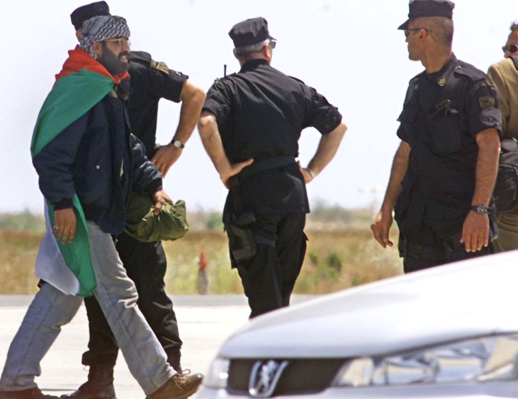 Anti-terrorist special police escort one of 13 deported Palestinian gunmen from a Royal Air Force Hercules at Larnaca airport in Cyprus on Friday, May 10, 2002. Their deportation was part of a deal worked out by the United States and the European Union to end Israel's five-week siege of Bethlehem's Church of the Nativity (photo credit: AP/Philip Mark)