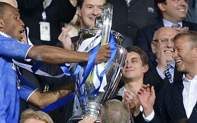 Chelsea's owner Roman Abramovich (right) applauds as striker Didier Drogba holds up the Champions League trophy, May 19, 2012. (AP Photo/Martin Meissner)