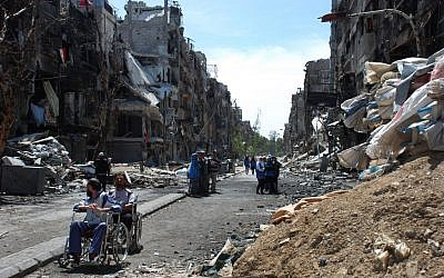 In this picture provided by the United Nations Relief and Works Agency for Palestine Refugees in the Near East (Unrwa.org), two men on their wheelchairs, wait to receive food supplies at a damaged street in the besieged Yarmouk refugee camp, on the southern edge of the Syrian capital Damascus, Syria, Thursday April 24, 2014 (AP)