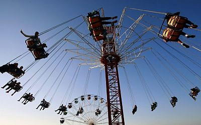 Palestinians enjoy a ride in an amusement park during the Eid al-Adha holiday, in the West Bank city of Jenin, Oct. 5, 2014. (photo credit: AP Photo/Mohammed Ballas)