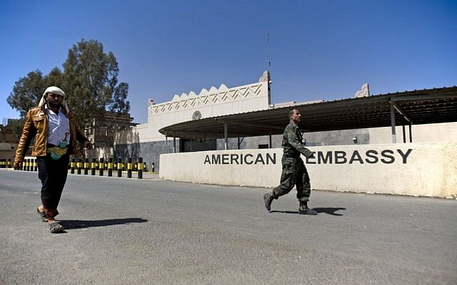 Houthi Yemenis walk past the gate of the main entrance of the closed U.S. embassy after Yemeni police opened the road in front of it, in Sanaa, Yemen, Wednesday, March 4, 2015 (photo credit: AP/Hani Mohammed)