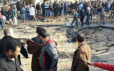 Egyptians gather around the crater following a bombing that struck a main police station in the capital of the northern Sinai province in el-Arish, Egypt, Sunday, April 11, 2015. (AP Photo/Muhamed Sabry)