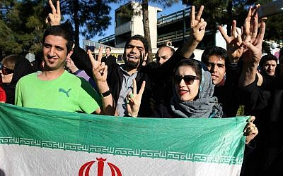 Iranians flash the Victory sign as they hold their country's flag while waiting for the arrival of Foreign Minister Mohammad Javad Zarif from Lausanne, Switzerland, at the Mehrabad airport in Tehran, Iran, on April 3, 2015. (AP/Ebrahim Noroozi)