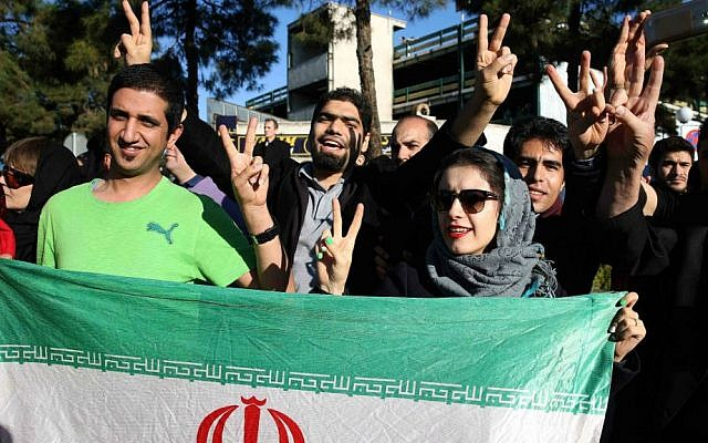 Iranians flash the victory sign as they hold their country's flag while waiting for arrival of Foreign Minister Mohammad Javad Zarif from Lausanne, Switzerland, at the Mehrabad airport in Tehran, Iran, Friday, April 3, 2015. (photo credit: AP/Ebrahim Noroozi)