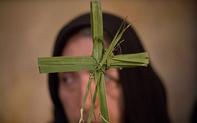 A Greek Orthodox woman holds a palm fond in the Church of the Holy Sepulchre, traditionally believed by many to be the site of the crucifixion and burial of Jesus Christ, during Orthodox Palm Sunday, in Jerusalem, Sunday, April 5, 2015. (photo credit: AP/Ariel Schalit)