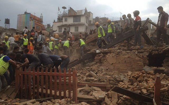 Rescuers clear the debris at Durbar Sqaure after an earthquake in Kathmandu, Nepal, Saturday, April 25, 2015. (Photo credit: AP/ Niranjan Shrestha)