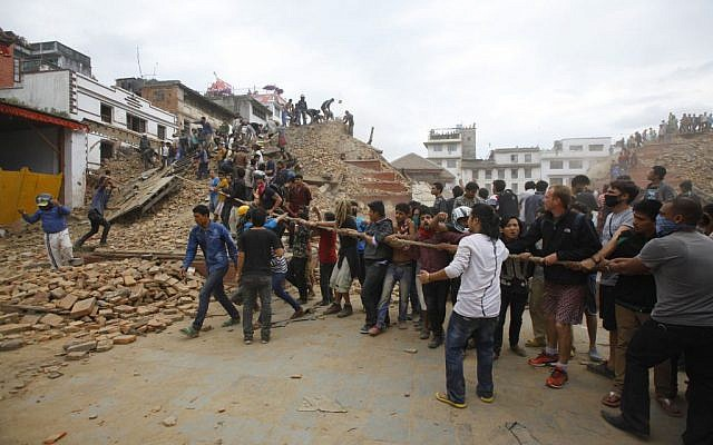 Volunteers help remove debris of a building that collapsed at Durbar Square, after an earthquake in Kathmandu, Nepal, Saturday, April 25, 2015. (photo credit: AP/Niranjan Shrestha)