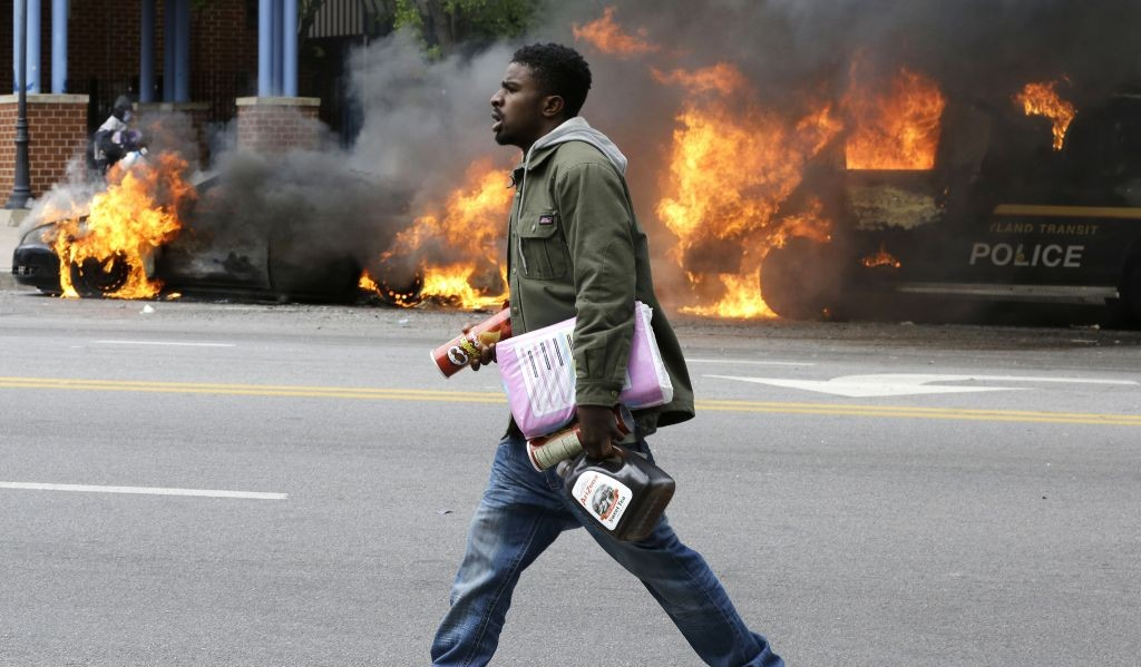 A man carries items from a store as police vehicles burn, Monday, April 27, 2015, after the funeral of Freddie Gray in Baltimore. Gray died from spinal injuries about a week after he was arrested and transported in a Baltimore Police Department van. (photo credit: AP/Patrick Semansky)
