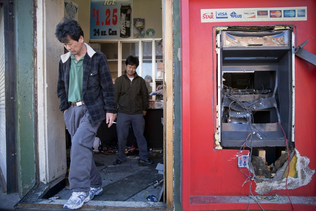 Jason Park, left, and his friend business owner Sung Kang, second left, leave his damaged store, Tuesday, April 28, 2015, in the aftermath of rioting following Monday's funeral for Freddie Gray, who died in police custody. (photo credit: AP Photo/Matt Rourke)