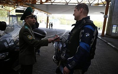 Belarus border guard checks the passport of a Russian biker at the Brest checkpoint on the Belarus-Polish border, April 27, 2015. (photo credit: AP/Sergei Grits)