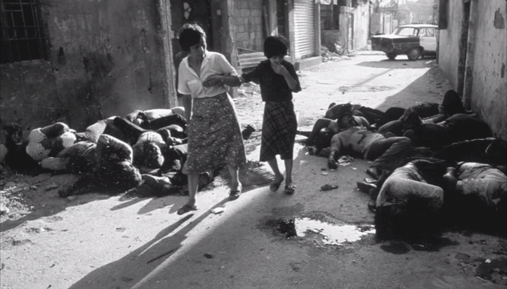 Two women pass a pile of individuals killed during the Lebanese Civil War. (screen capture: YouTube)