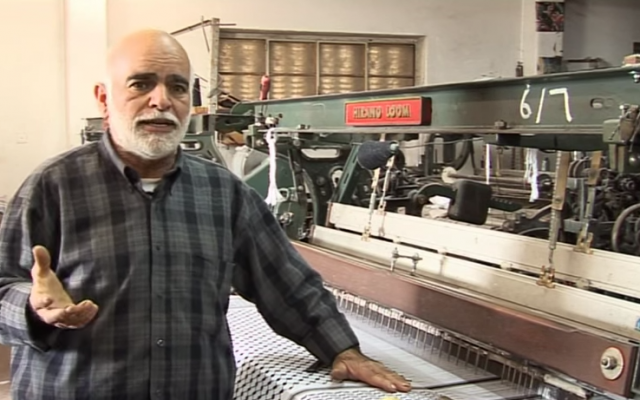 A loom worker in a Hebron-based textile mill that produces Palestinian-made keffiyehs. (screen capture: YouTube/Howard Johnson)