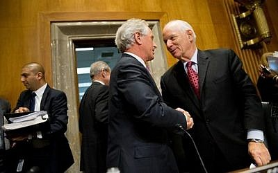 Senate Foreign Relations Committee Chairman Sen. Bob Corker, center, shakes hands with the committee's ranking member Sen. Ben Cardin, on Capitol Hill in Washington, Tuesday, April 14, 2015, after the committee passed the Iran Nuclear Agreement Review Act of 2015. (photo credit: AP Photo/Andrew Harnik)
