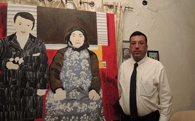 Kevork Nalbandian, a lawyer and social worker who is on the planning committee for the 100th anniversary in Jerusalem, stands in his home next to a painting made by a 17-year-old local Armenian teenager dealing with themes of memory and Armenian identity.  (Melanie Lidman/Times of Israel)