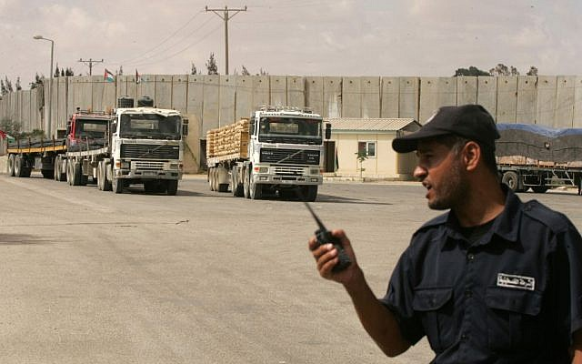 A Palestinian policeman loyal to Hamas stands guard as trucks transporting construction materials enter the Gaza Strip through the Kerem Shalom Crossing on September 22, 2013. (photo credit: Abed Rahim Khatib/Flash90)
