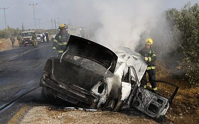 An Israeli car set ablaze by a Molotov Cocktail thrown near the Palestinian village of Tuqua in the West Bank, November 8, 2013 photo credit: Gershon Elinson/Flash90
