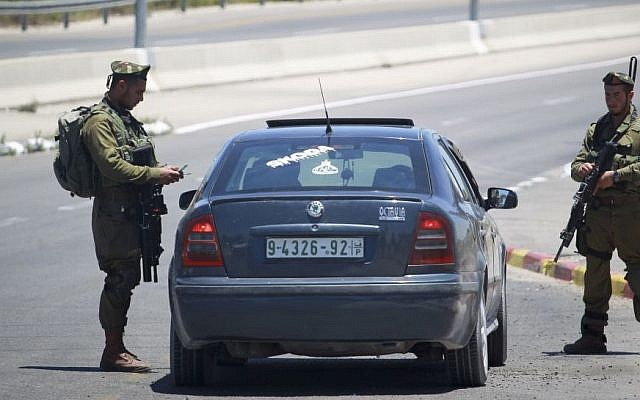 Israeli soldiers check Palestinian cars at the Gush Etzion Intersection in the West Bank, June 15, 2014. (photo credit: Hadas Parush/Flash90)
