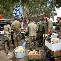 IDF reserve soldiers seen getting food in a staging area near the border with Gaza in southern Israel on July 20, 2014, during Israel's Operation Protective Edge. (Moshe Shai/Flash90)