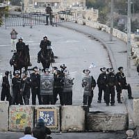 Israeli Border Police stand guard next to new cement blocks placed at the entrance to Issawiya in East Jerusalem during a demonstration against the neighborhood's closure, November 12, 2014 (photo credit: Hadas Parush/Flash90)