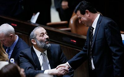 Shas party leader Aryeh Deri shakes hands with Joint Arab list head Ayman Odeh during the swearing-in ceremony for the 20th Knesset, March 31, 2015. (Photo credit: Miriam Alster/Flash90)