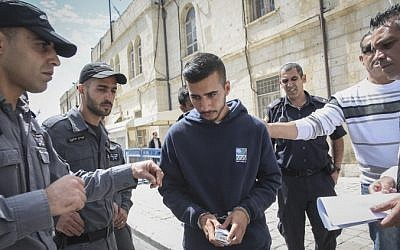 Niv Asraf (center), a 22-year-old from Beersheba, is seen at the Jerusalem Magistrate's Court on April 3, 2015, a morning after he was found in Kiryat Arba after being falsely reported as missing. (Hadas Parush/Flash90)