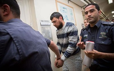 Police escort Khaled Koutineh, who rammed his car into Israeli pedestrians, to a hearing at the Magistrate's Court in Jerusalem. April 16, 2015. (photo credit: Miriam Alster/FLASH90)