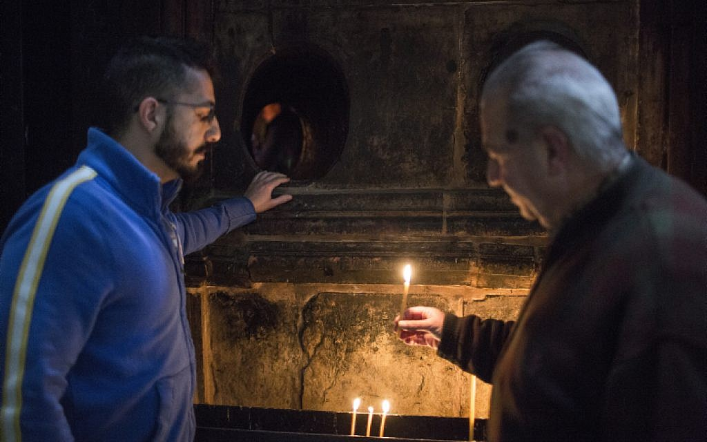 Soghomon Toumayan (R) and his son Michael (L), talk as they stand by the hole to the Chamber of the Tomb of Christ at the Church of the Holy Sepulchre in Jerusalem's Old City, on April 15, 2015.  (photo credit: Hadas Parush/Flash90)