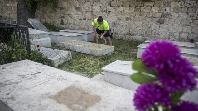 Youth clean the Armenian Cemetery on Mount Zion near the Armenian Quarter of Jerusalem's Old CIty, on April 15, 2015, ahead of prayers that will take place at the cemetery in honor of the victims of the Armenian Genocide. (Hadas Parush/Flash90)