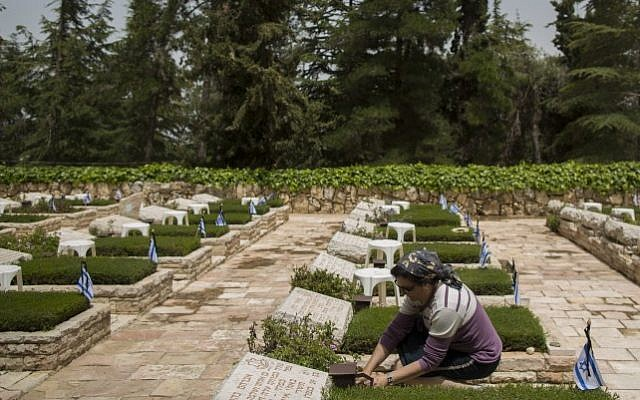 An Israeli woman lights a candle at a grave in Mount Herzl Military Cemetery in Jerusalem on April 20, 2015 (Photo credit: Yonatan Sindel/Flash90)