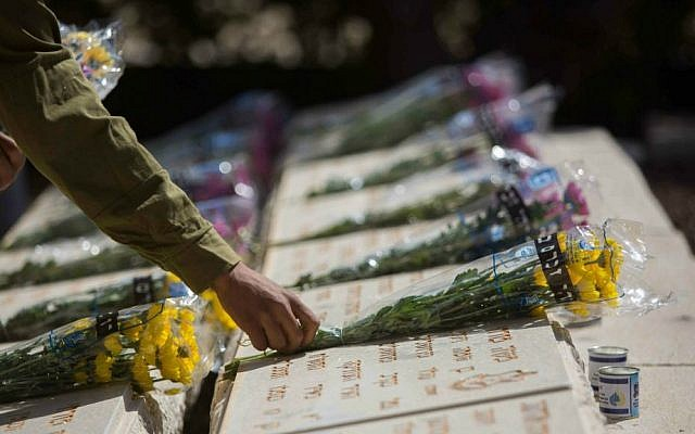 An IDF soldier places flowers on the grave of fallen soldiers during a ceremony held at the Mount of Olives in Jerusalem ahead of Memorial Day, April 21, 2015. (photo credit: Yonatan Sindel/Flash90)