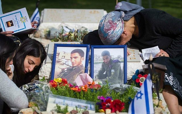 Bereaved Israelis mourn next to the graves of fallen soldiers at the Mt. Herzl military cemetery in Jerusalem, April 22, 2015. (Miriam Alster/Flash90)