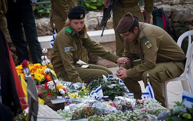 Israeli soldiers mourn next to the graves of fallen soldiers at the Mt. Herzl military cemetery in Jerusalem, April 22, 2015. (Miriam Alster/Flash90)