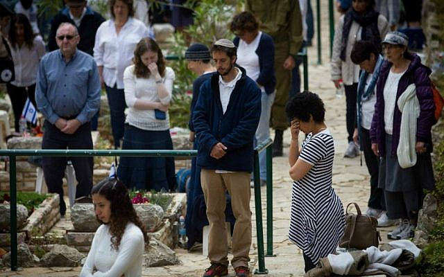 Israelis stand in silence next to the graves of IDF soldiers at the Mt. Herzl military cemetery in Jerusalem, April 22, 2015. (Miriam Alster/Flash90)