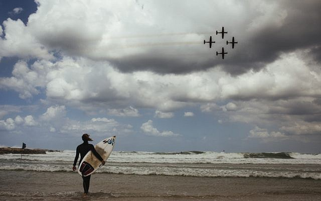 A surfer watches an Israeli Air Force aerial acrobatics demonstration on the country's 67th Independence Day at a Tel Aviv beach, April 23, 2015. (Matanya Tausig/Flash90)